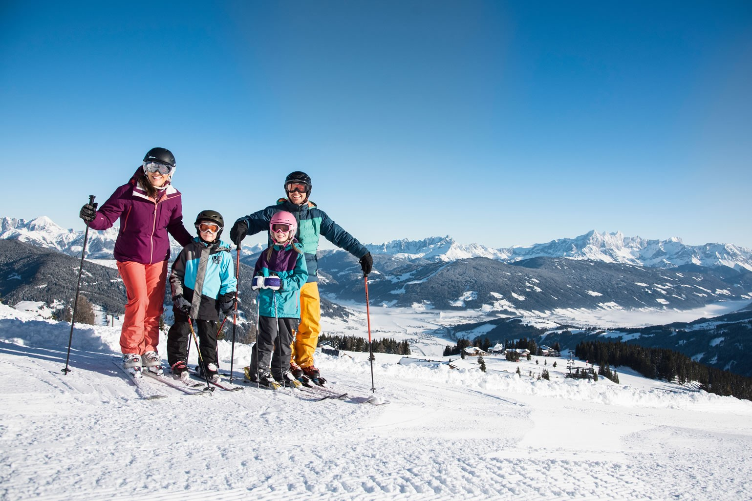 Family on the ski piste in the ski area Flachau